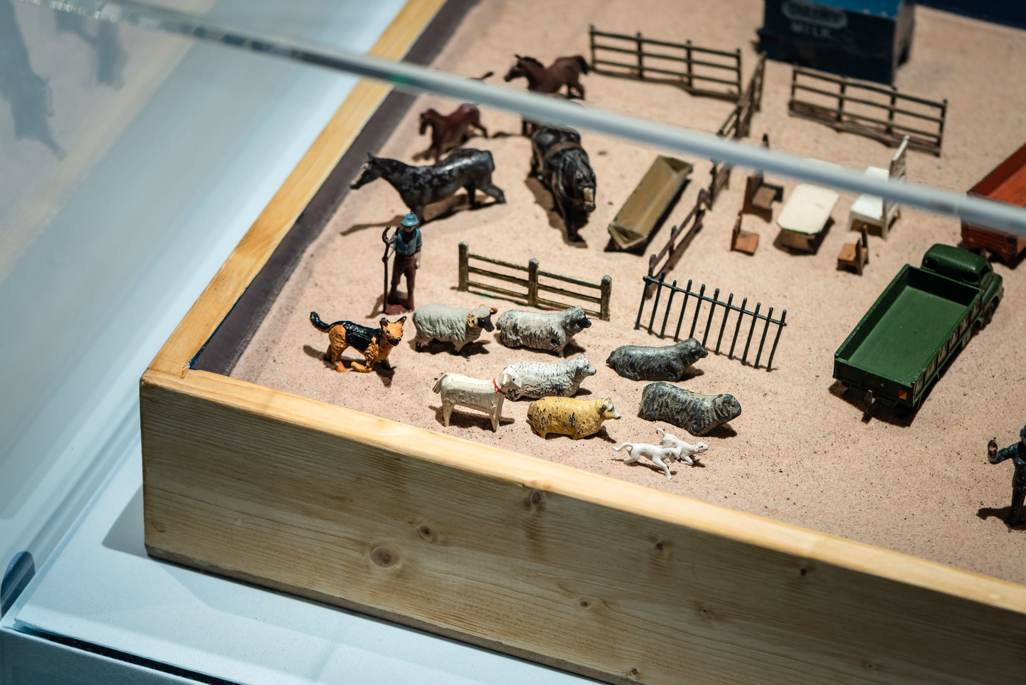 Miniature plastic replica of a farm including animals, fences and trucks