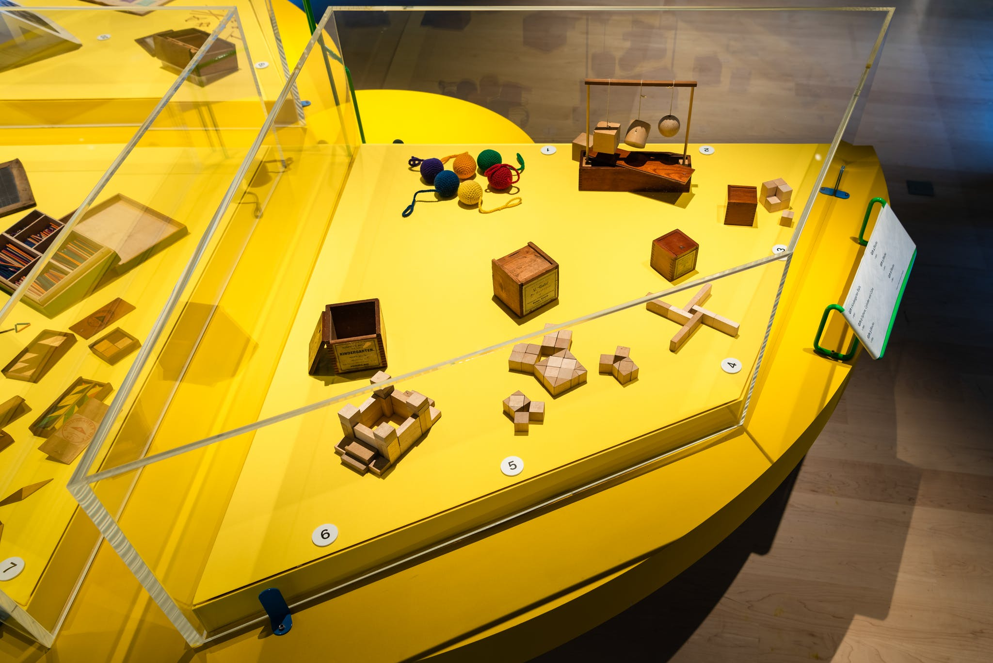 Photograph of an exhibition display case with a bright yellow base. Inside the case are several small wooden toys in various shapes and 6 balls of coloured wool.