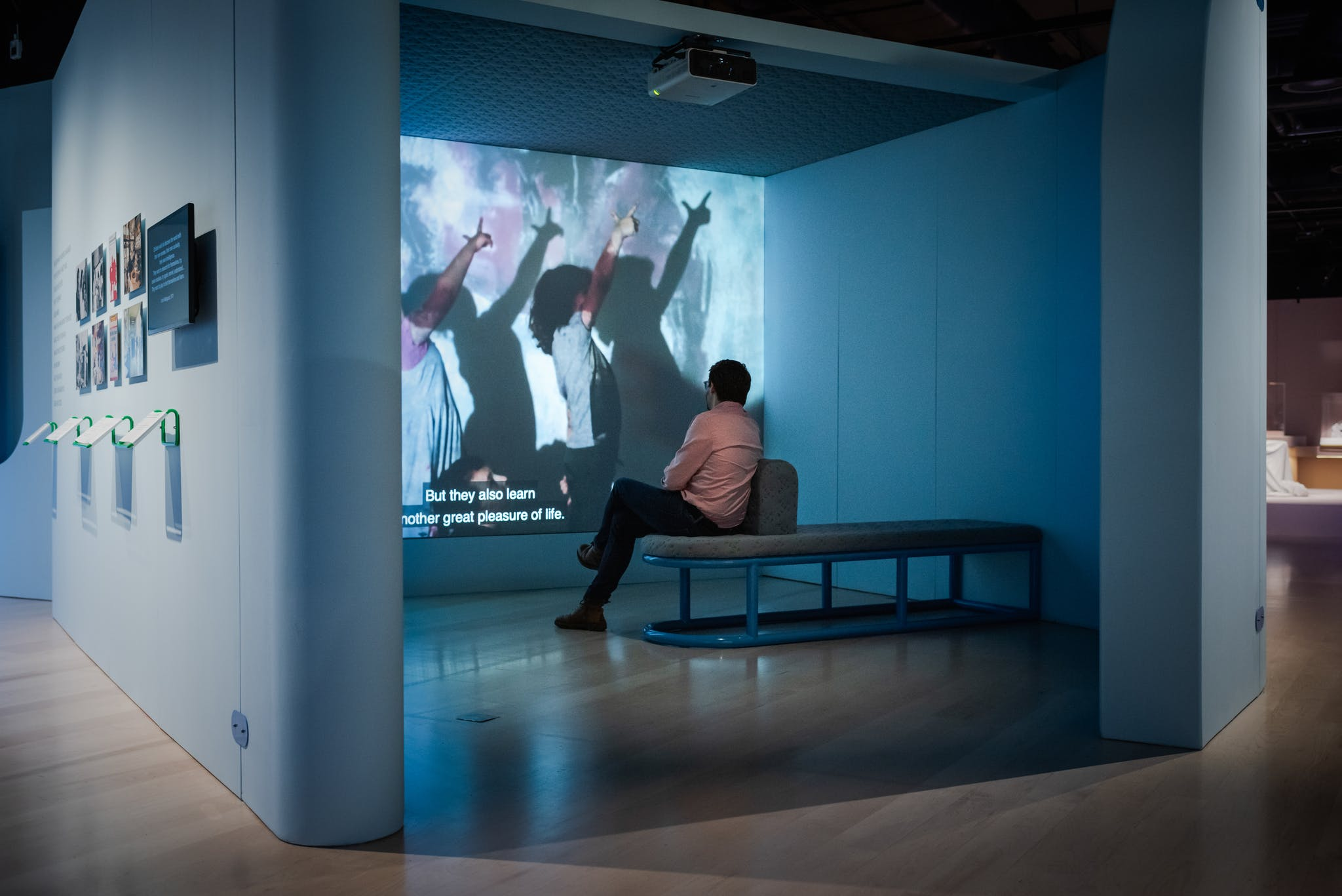 A man in a suit leaning against the wall watching a video in the exhibition hall