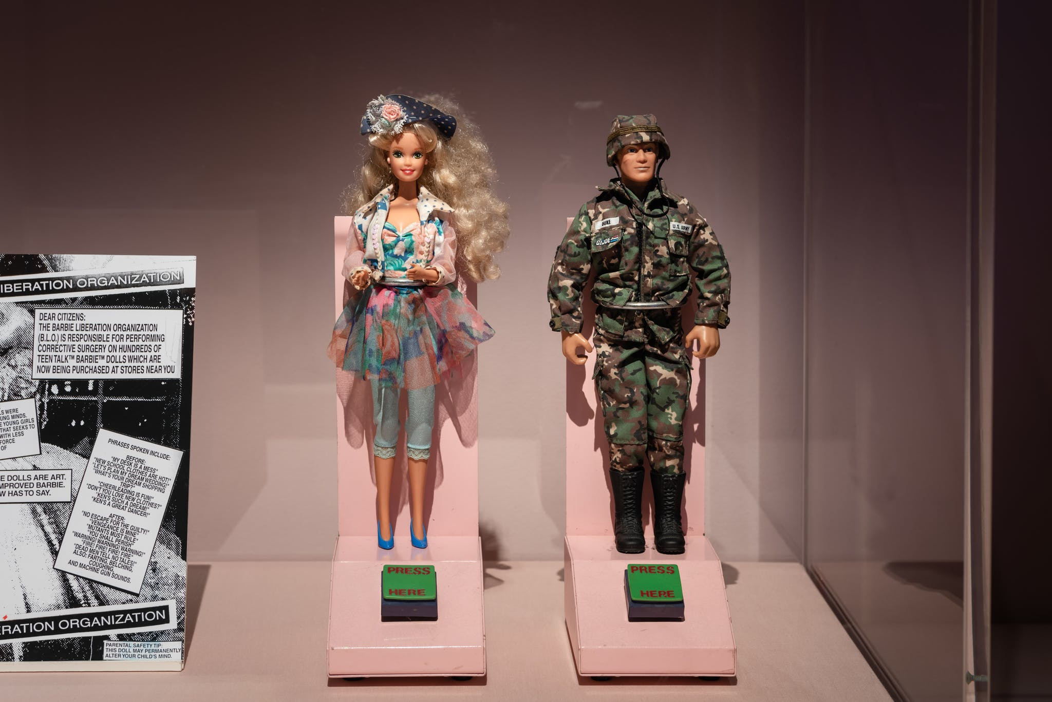 A close up of an exhbition case with a Barbie doll and Ken doll from the 1970s next to a posted about Igor Vamos' Barbie Liberation Organization.