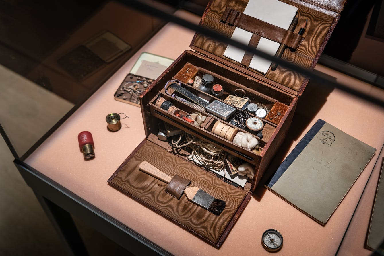 A close up of an exhibit display case which inside has an open wooden box containing string, buttons and other small trinkets