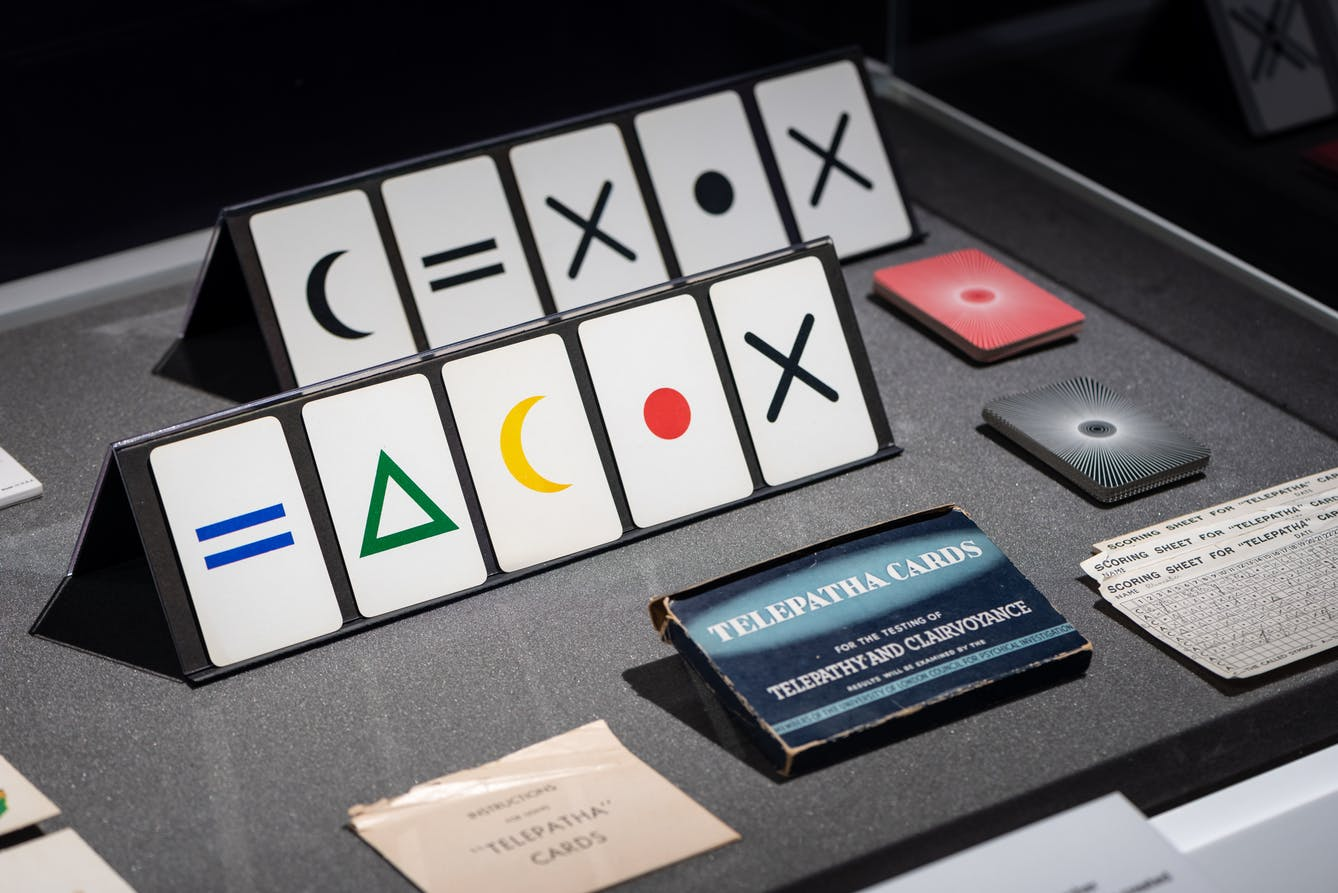 An exhibition glass case displaying a set of Telepatha cards  and the box that they would put in.