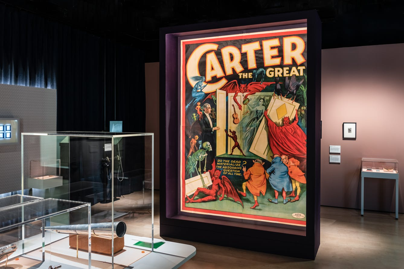 A large colourful poster promoting Carter the Great in a glass case.