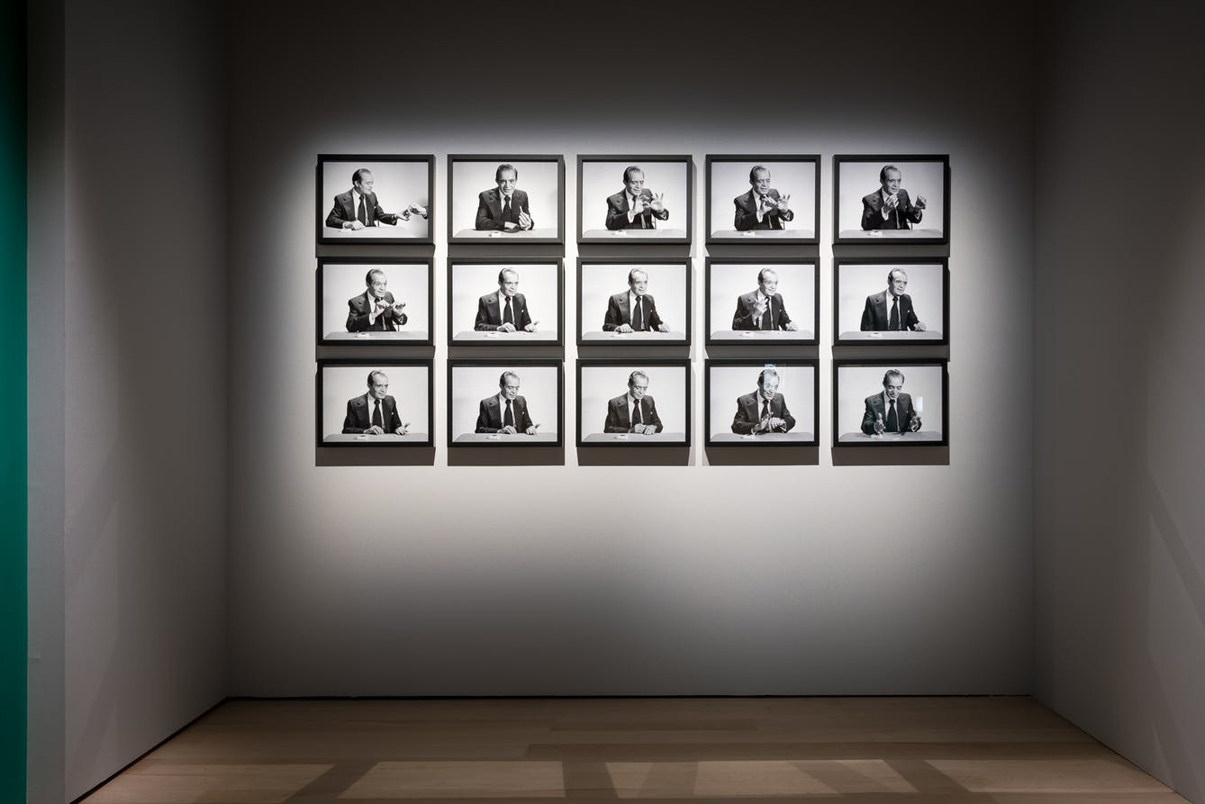 A white wall 15 picture frames with black and white photos breaking down from start to finish a man performing a magic trick.
